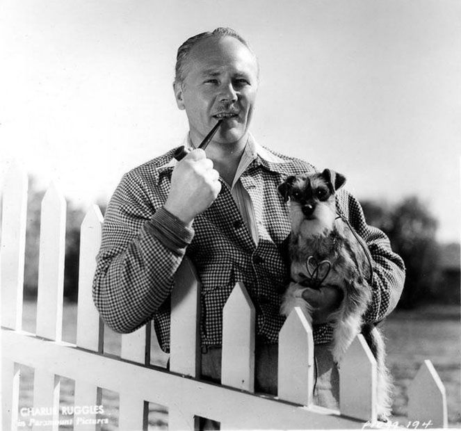 0 charles ruggles smoking his pipe and holding his dog by a fence