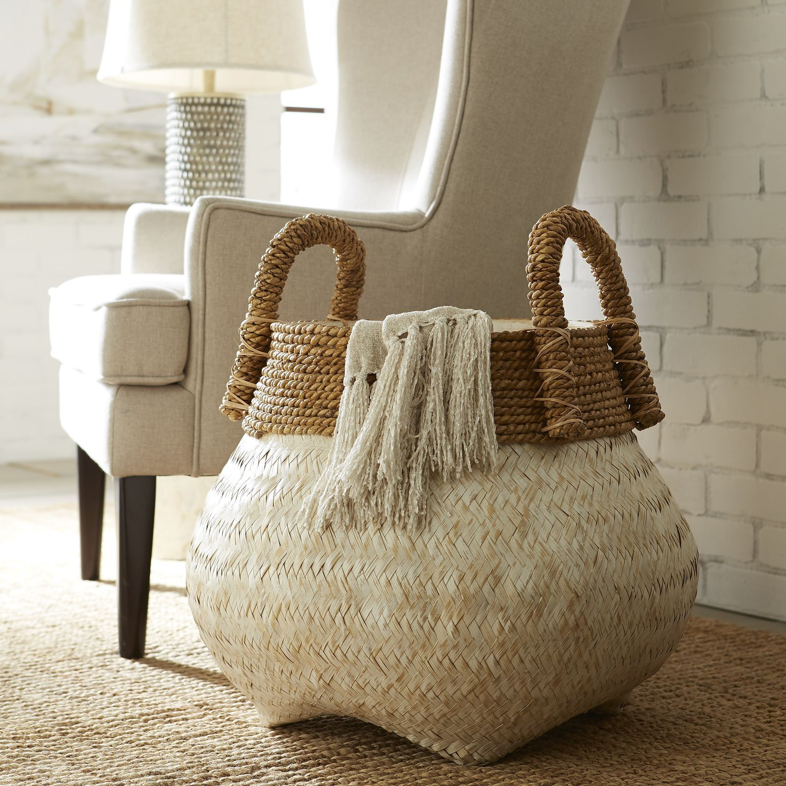 Storage goes global with our belly basket. Hand-woven of bamboo by Indonesian artisans, it features a stunning herringbone-inspired design. For extra strength and visual contrast, the rim and handles are crafted from twisted banana leaf. Perfect for stowing blankets, bath towels or toys.