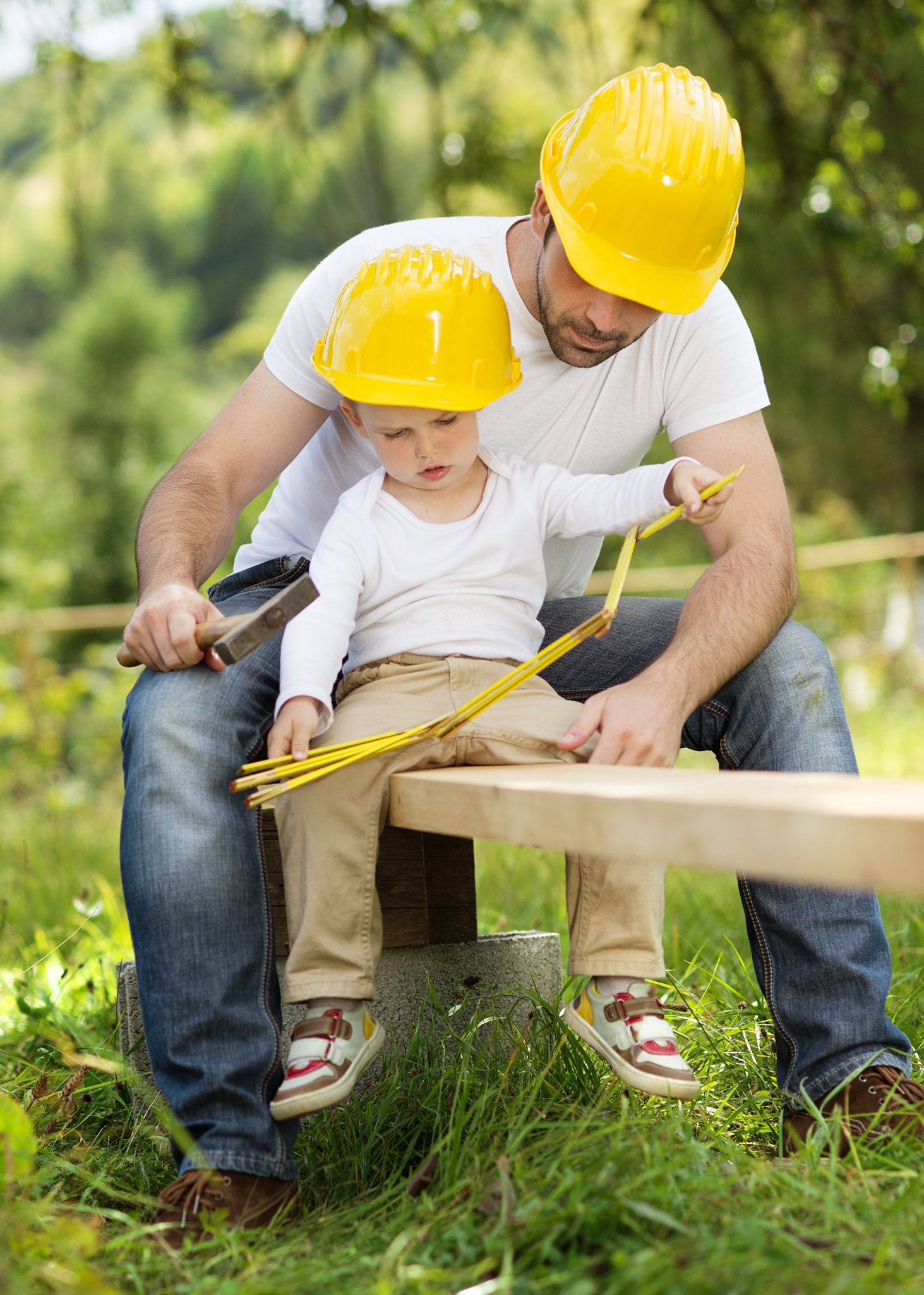 Little Son Helping His Father With Building Work United By