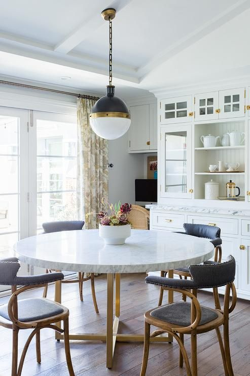 Vintage Black Leather And Wood Dining Chairs Sits Around A Round Marble And Brass Dining With Images Contemporary Kitchen Tables Brass Dining Table Round Dining Room Table