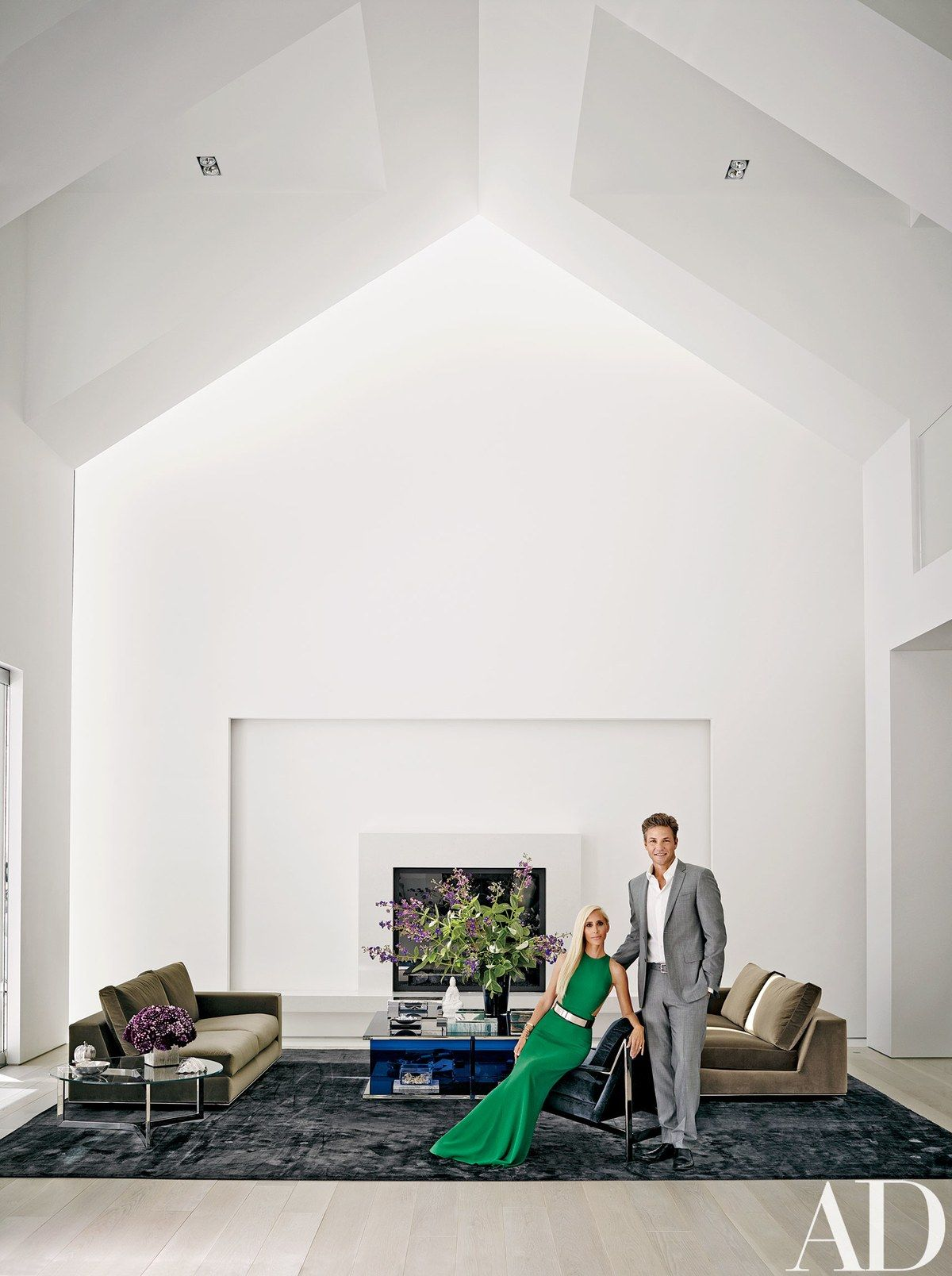 The couple in the living area, where a Minotti sofa is grouped with an Alexandra von Furstenberg cocktail table and a vintage Milo Baughman chair; the fireplace surround is Caesarstone.