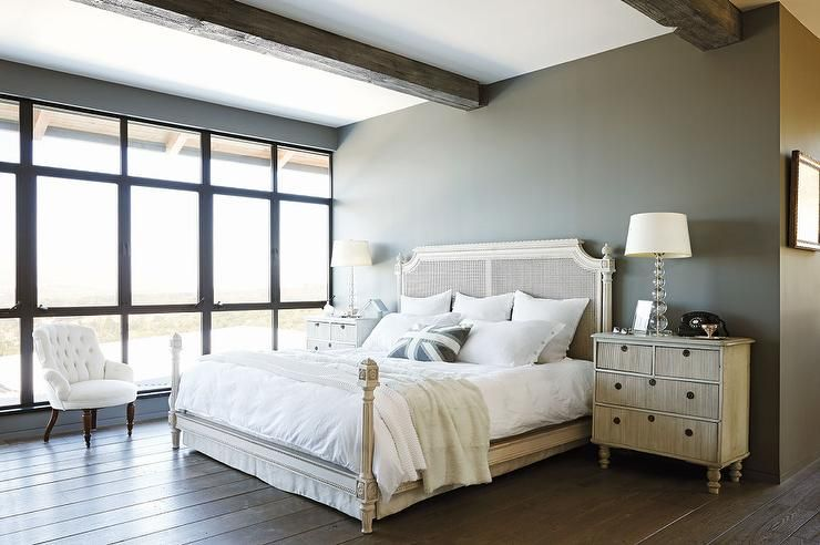 Captivating Modern French Bedroom Features Rustic Wood Beams Over A White Cane Bed  Dressed In Plush White