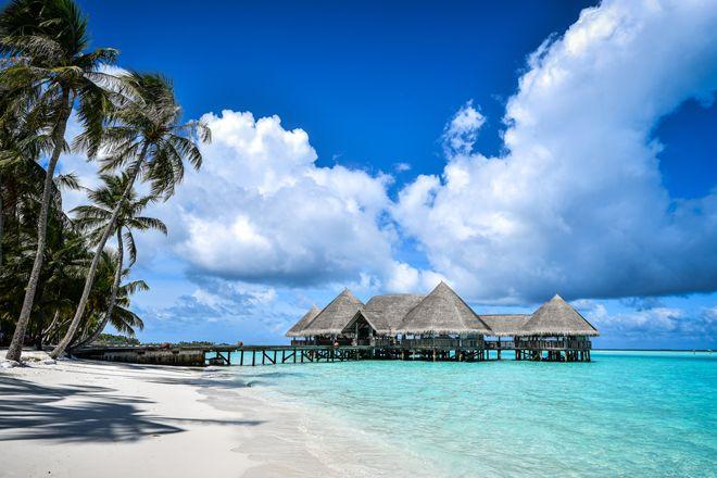 Lagon turquoise sable fin et cabanes sur pilotis aux - Maison sur pilotis maldives ...