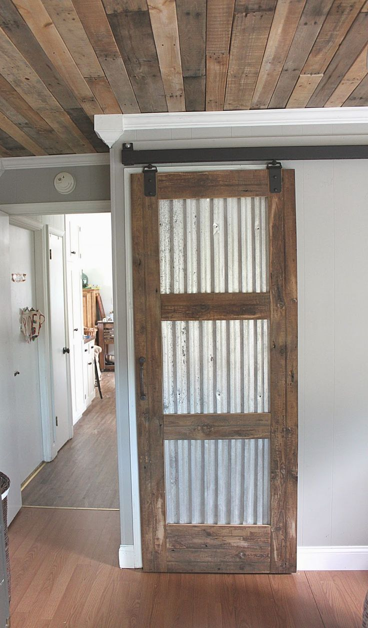 Sheet metal and pallet wood turned into a diy barn door home