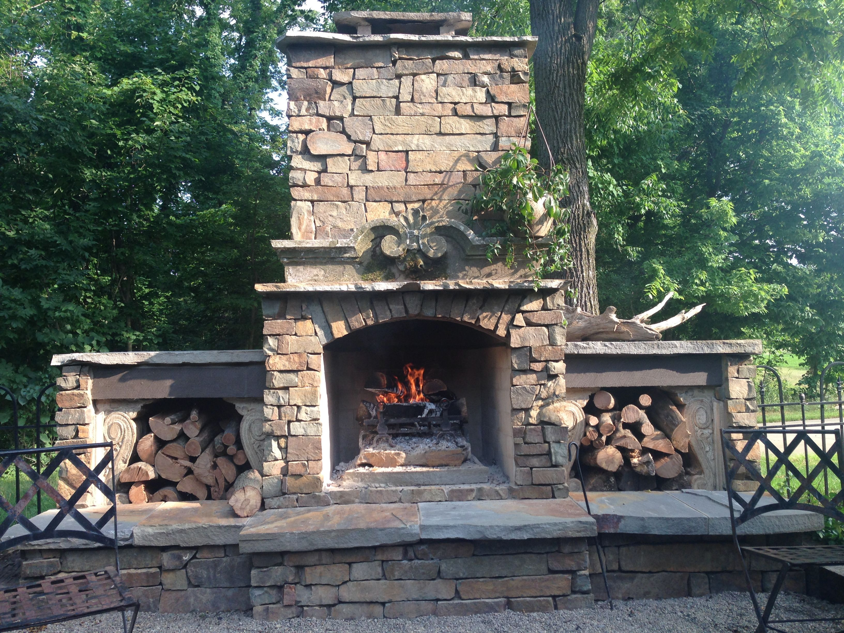 Outdoor king arthur fireplace with side storage boxes for Outdoor stone fireplace designs