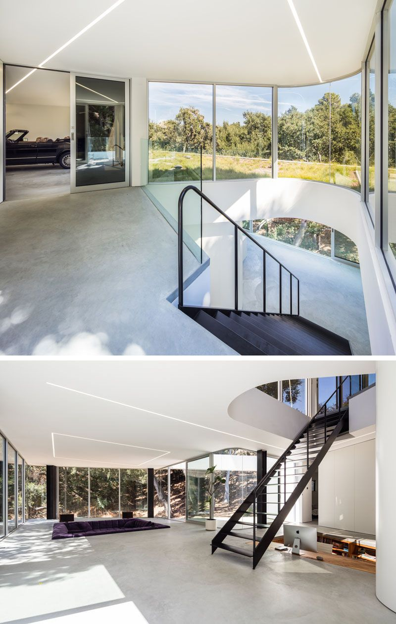 Next to the garage in this modern house are stairs that lead down to the living level of the house and sunlight from the curved windows is able to funnel