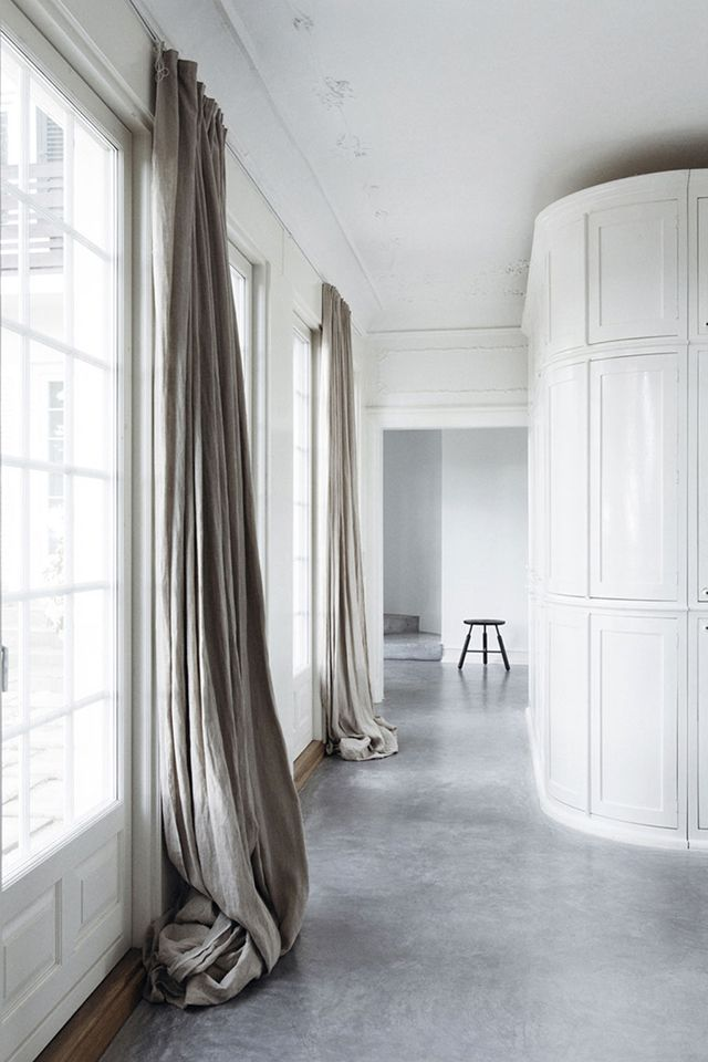 extralong hanging linen curtains add a softness to a minimal interior the off