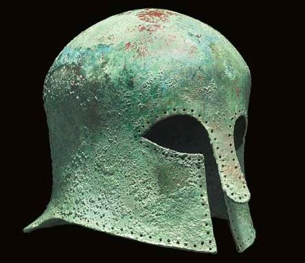 Corinthian helmet, late 7th century B.C. Of domed form with flaring flange at rear, slender nose-guard, pierced with multiple holes around the perimeter for lining attachment, restored flange and tip of cheekpieces, 21.6 cm high. Private collection, from Christie's auction