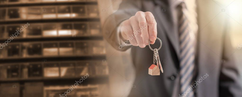 Estate agent offering house keys multiple exposure  Stock Photo