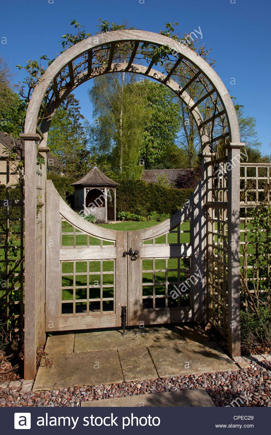 Garden feature Arch with gates leading into lawn area and fe…