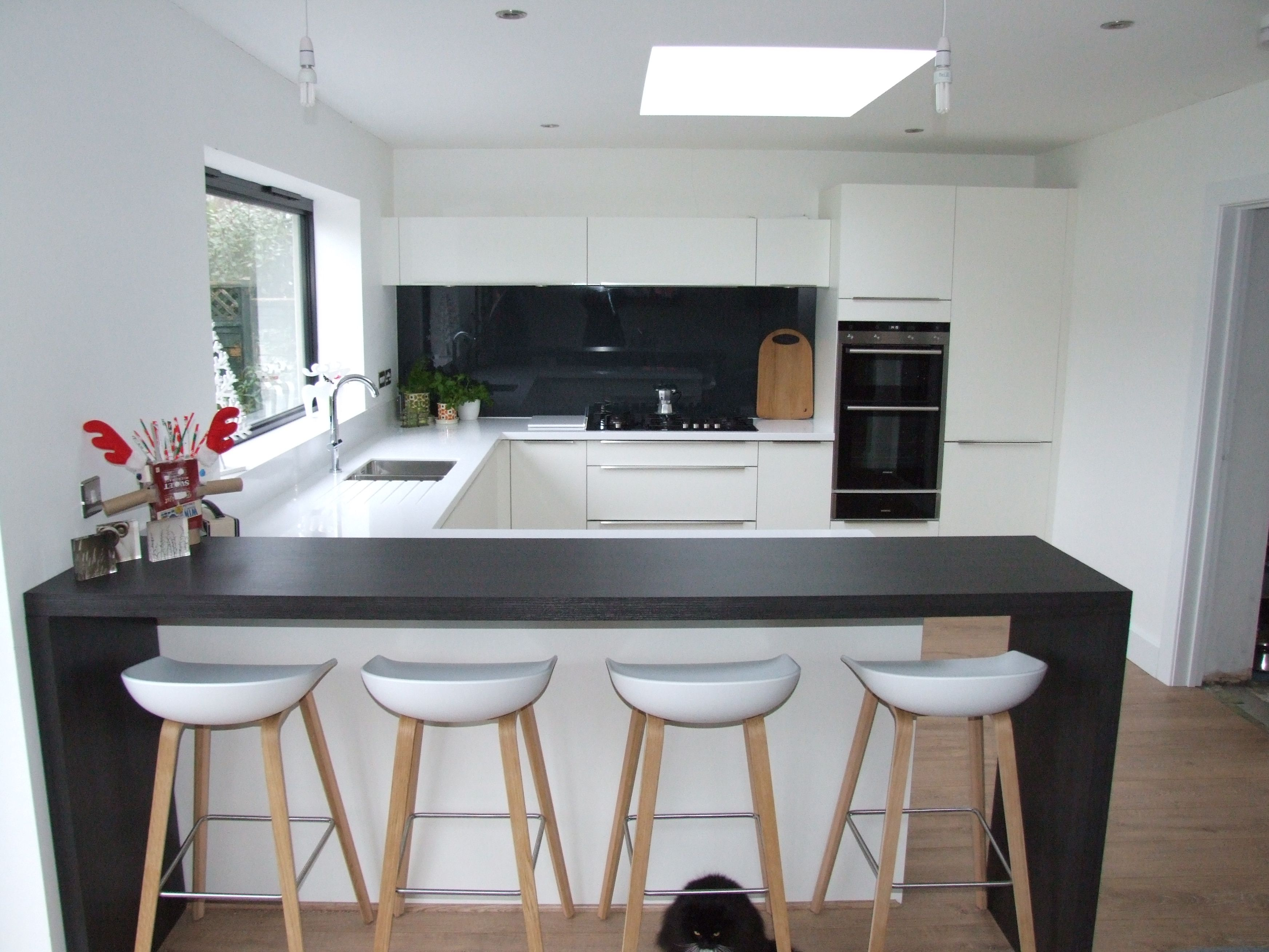 this striking white kitchen consists of matt white cabinetry and