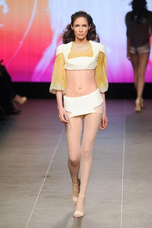 Julien Fournie short neoprene skirt and neoprene brassiere with organza sleeves.