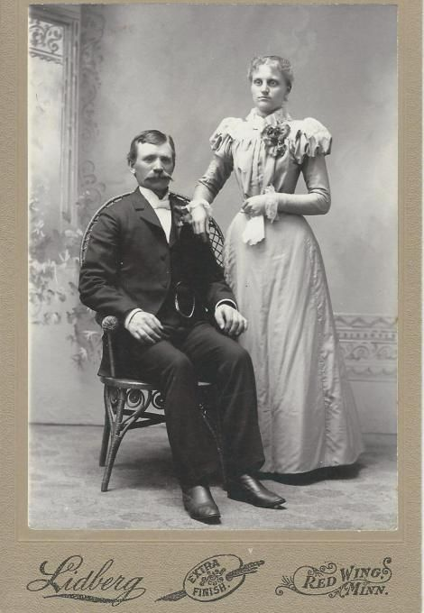 An unidentified well dressed couple pose for their portrait at the Lidberg studio in Red Wing, Minnesota. Note the woman's thin waist, indubitably assisted by a very tight corset. She and her husband are both wearing corsages which hints that this image is a wedding photograph. Andrew Lidberg emigrated from Sweden and arrived in Michigan in 1877. He opened a photographic studio in Red Wing in 1892.