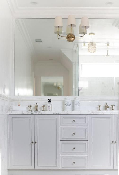 Photo of Stunning white and gray bathroom features white paint on top half of walls and m…