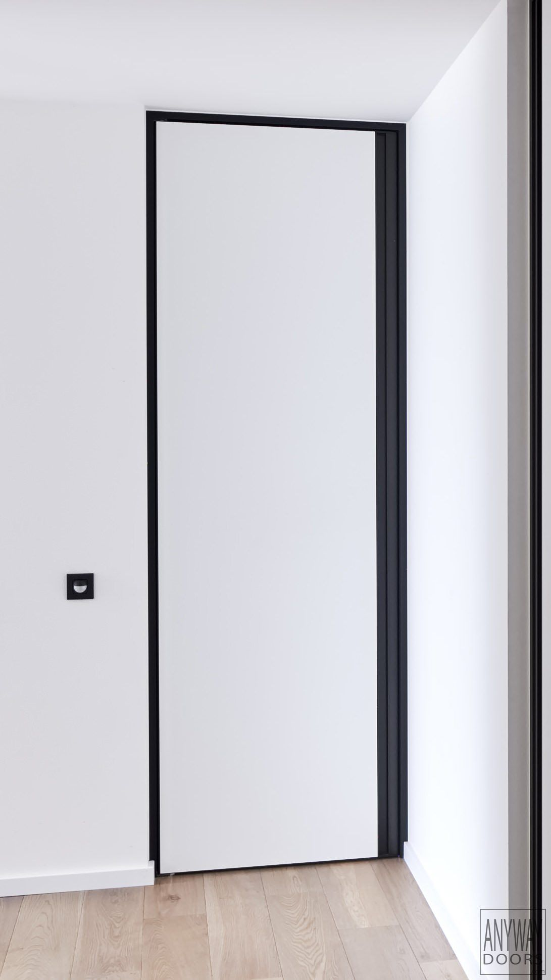 White interior door with a black door frame and built-in handle ...