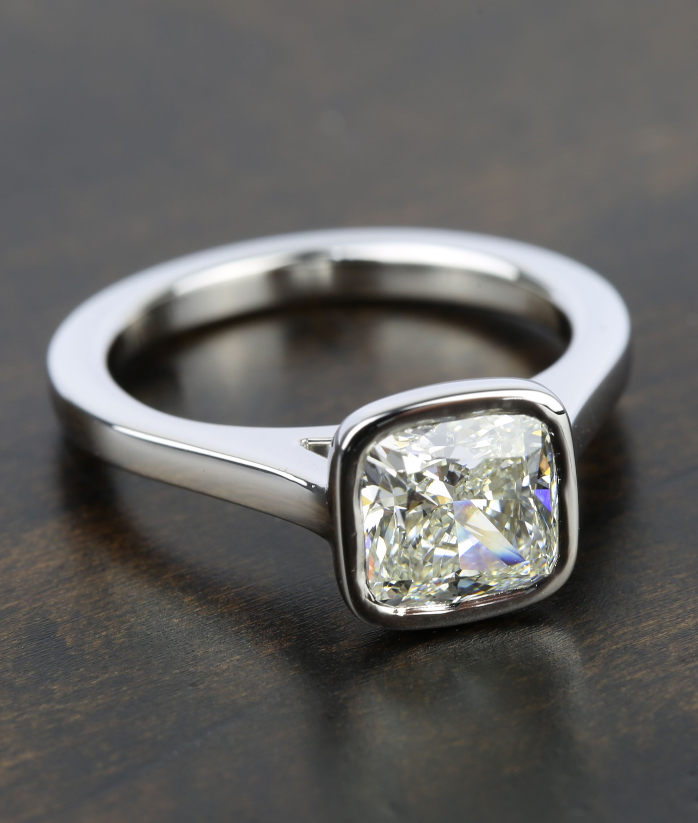 16721c8066c1 Additionally the bezel setting gives the allusion of added size to the  center Cushion cut diamond.