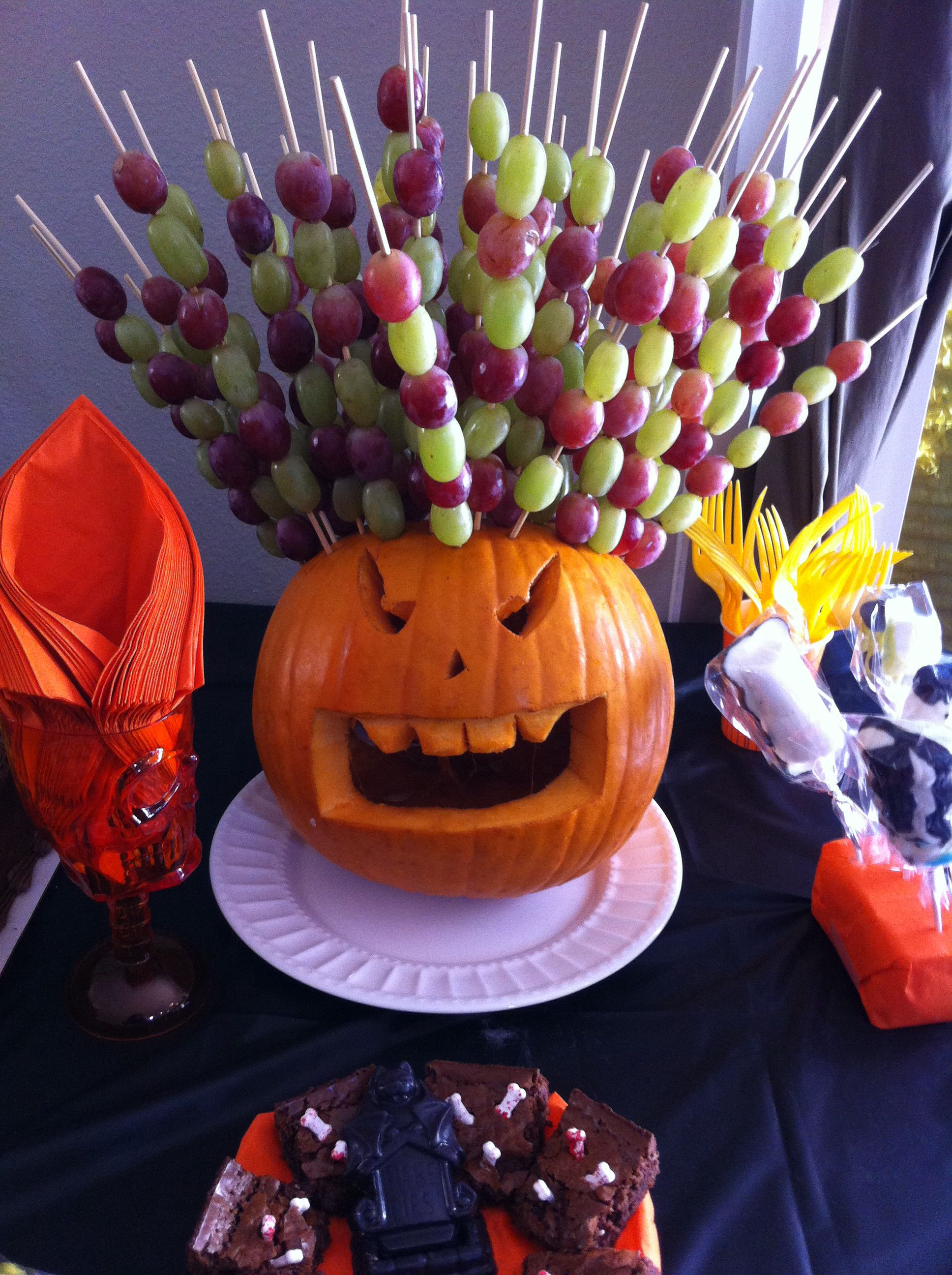 Carved pumpkin used to serve fruit at a Halloween party