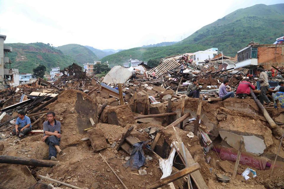 Earthquake victims sit amid the debris of collapsed houses in Ludian county in Zhaotong, in southwest China's Yunnan province on August 4, 2014...
