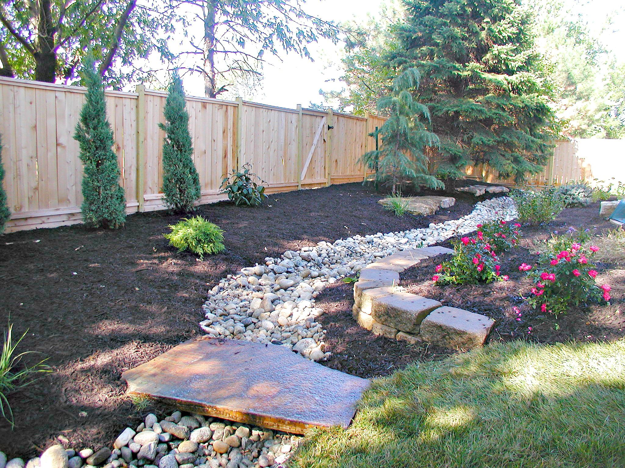Problems With Drainage Issues In Your Yard This Customer Had A Dry Creek Bed Added Along With Plantings A Dry Creek Bed Backyard Landscaping Designs Dry Creek