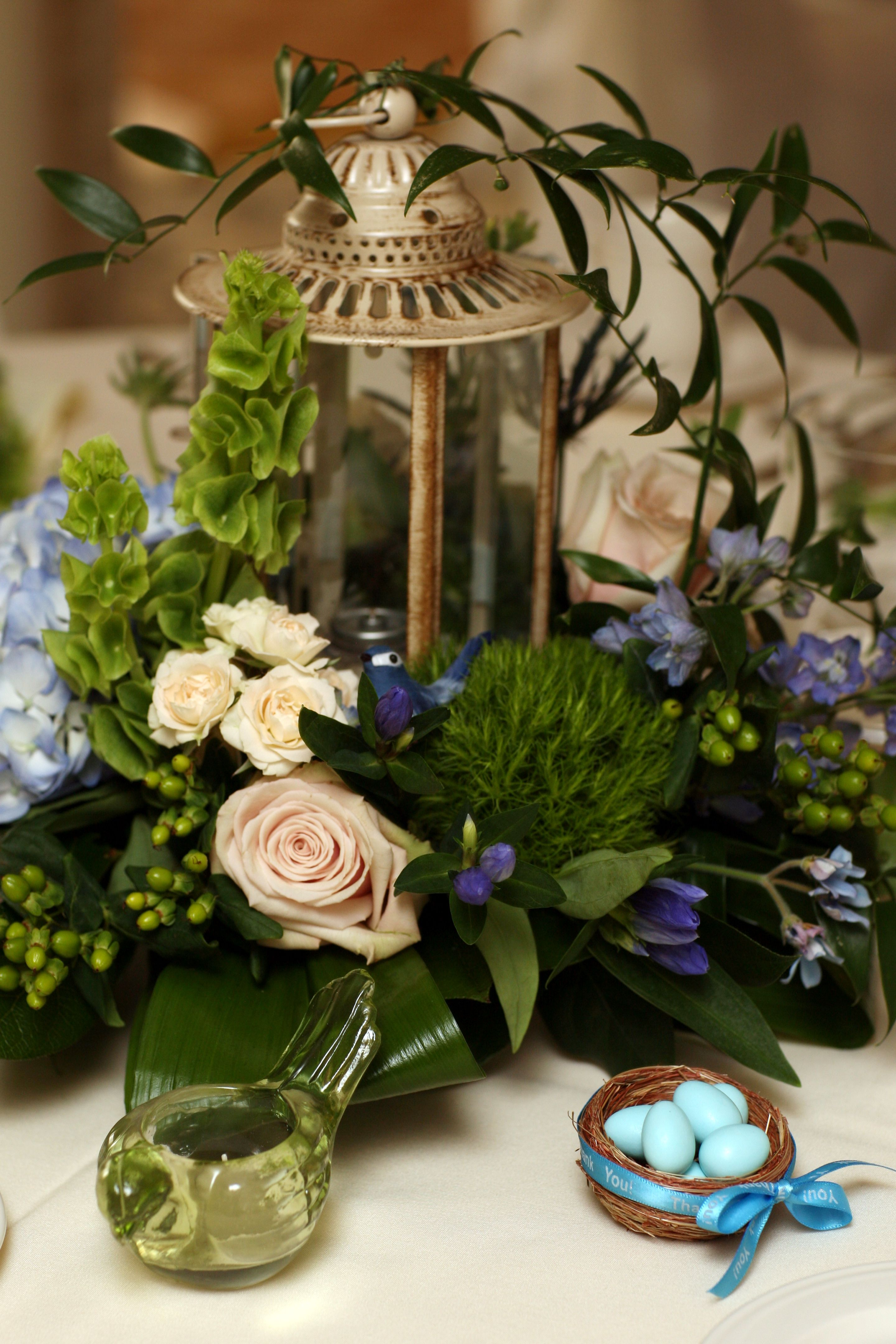 Wedding Centerpiece With A Garden Theme. Lantern, An Abundance Of Flowers  And Even A