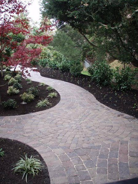 "A beautiful pathway winding through a lush landscape.  We love the ""pop"" of the red Japanese maple tree."