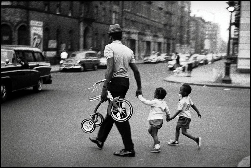 a man guides two children across the street in harlem in 1956 (leonard freed)