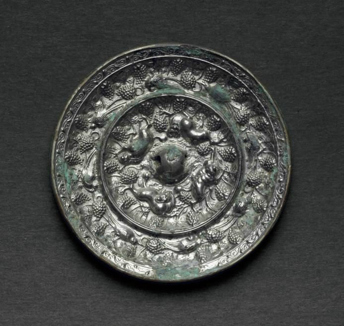A silvery bronze circular  'Lion and grapevine' mirror, Tang dynasty (AD 618-907).