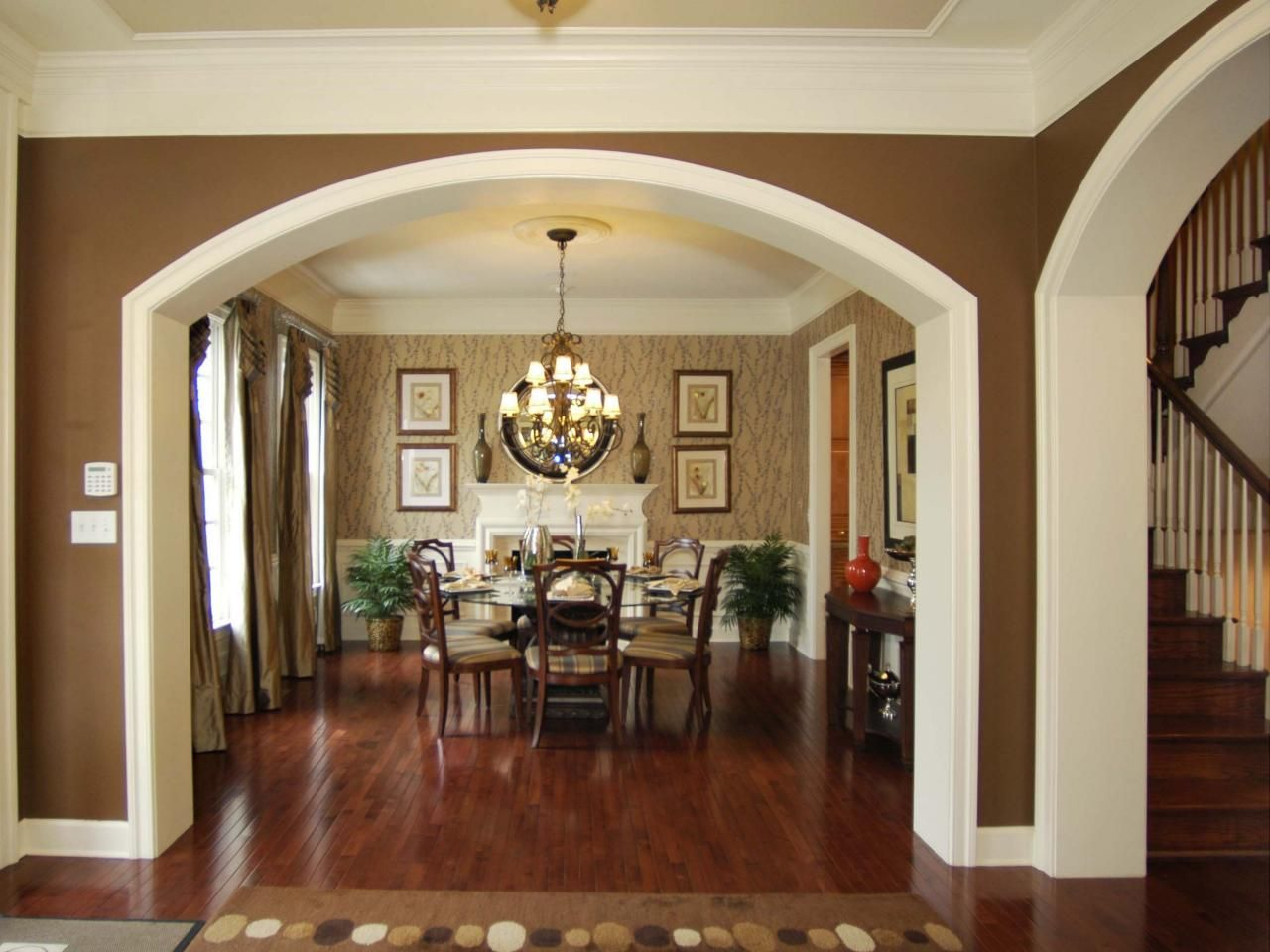 Rich brown hardwood floors create a seamless transition to the dining area, complete with classic wood dining chairs and large chandelier. Beige wallpaper with a subtle pattern provides contrast to the bold white crown molding and fireplace.