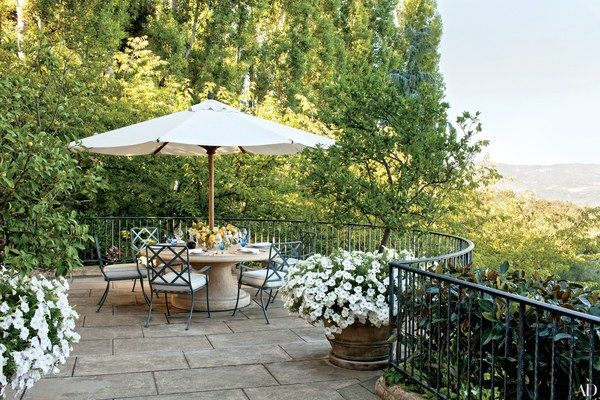 A Sunbrella-fabric umbrella shades a dining area on a terrace overlooking Sonoma Valley.