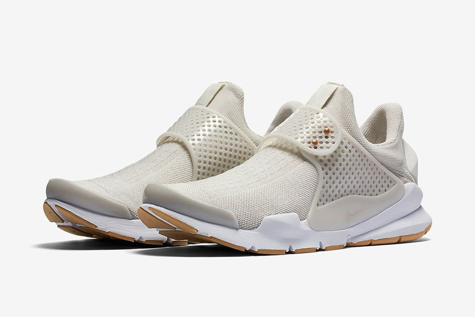 check out 31093 2af92 The laceless Nike Sock Dart is draped in a light beige for the mesh and  canvas upper, with bronze at the strap pegs and a contrasting crisp white  midsole.
