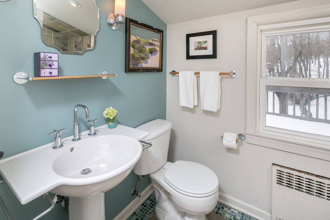 The main bathroom features a white Porcher sink with nickel fixtures ...