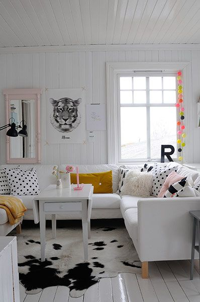 Credit: Marianne Wie In the living room, a plain Ikea sofa is cheered up with cushions from OYOY, HM Home and Tas-Ka, as well as homemade ones. Ikea sells cow hide rugs, and the multicoloured baubles by the window are by
