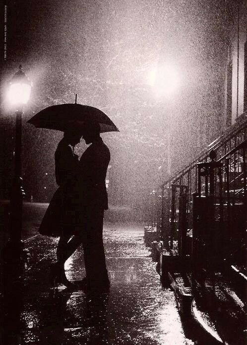 Silhouette Of A Couple Embracing Under An Umbrella In The Rain