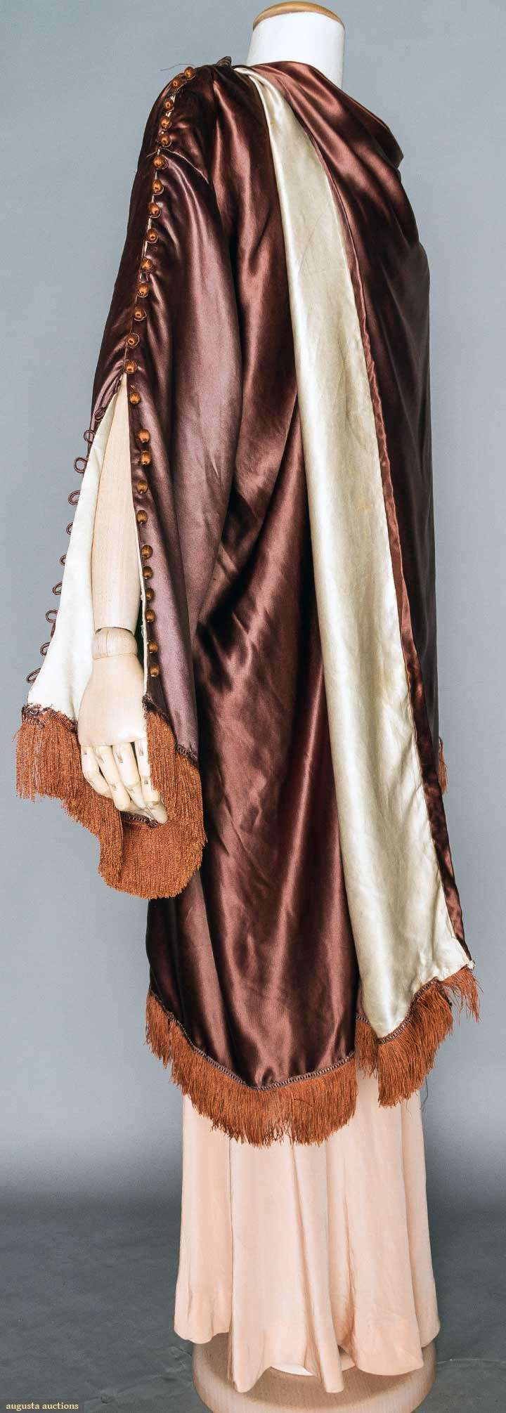 POIRET SILK EVENING WRAP, PARIS, 1917. Unlabeled, the MET & FIT museums have same garment in different color. Eggplant silk charmeuse, white silk charmeuse lining, wide sleeves w/ rust thread ball buttons from shoulders to rust fringed sleeve hem, wide F panel wraps over right shoulder, 2 fringed tabs fall to back at shoulders. Sideway