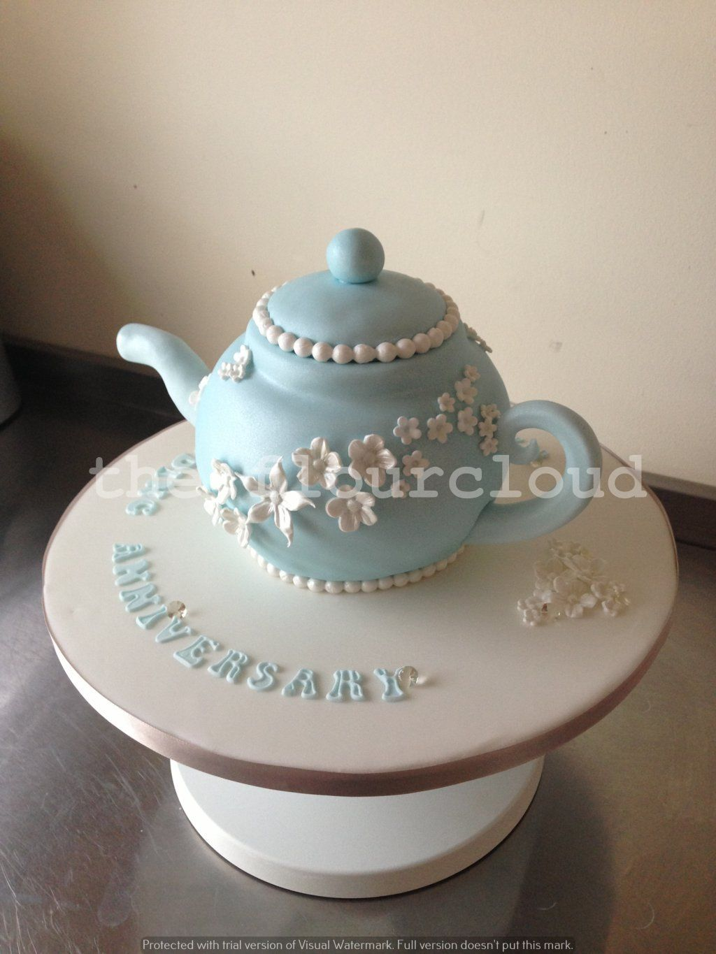 A delicate blue teapot with beautiful white flowers as an