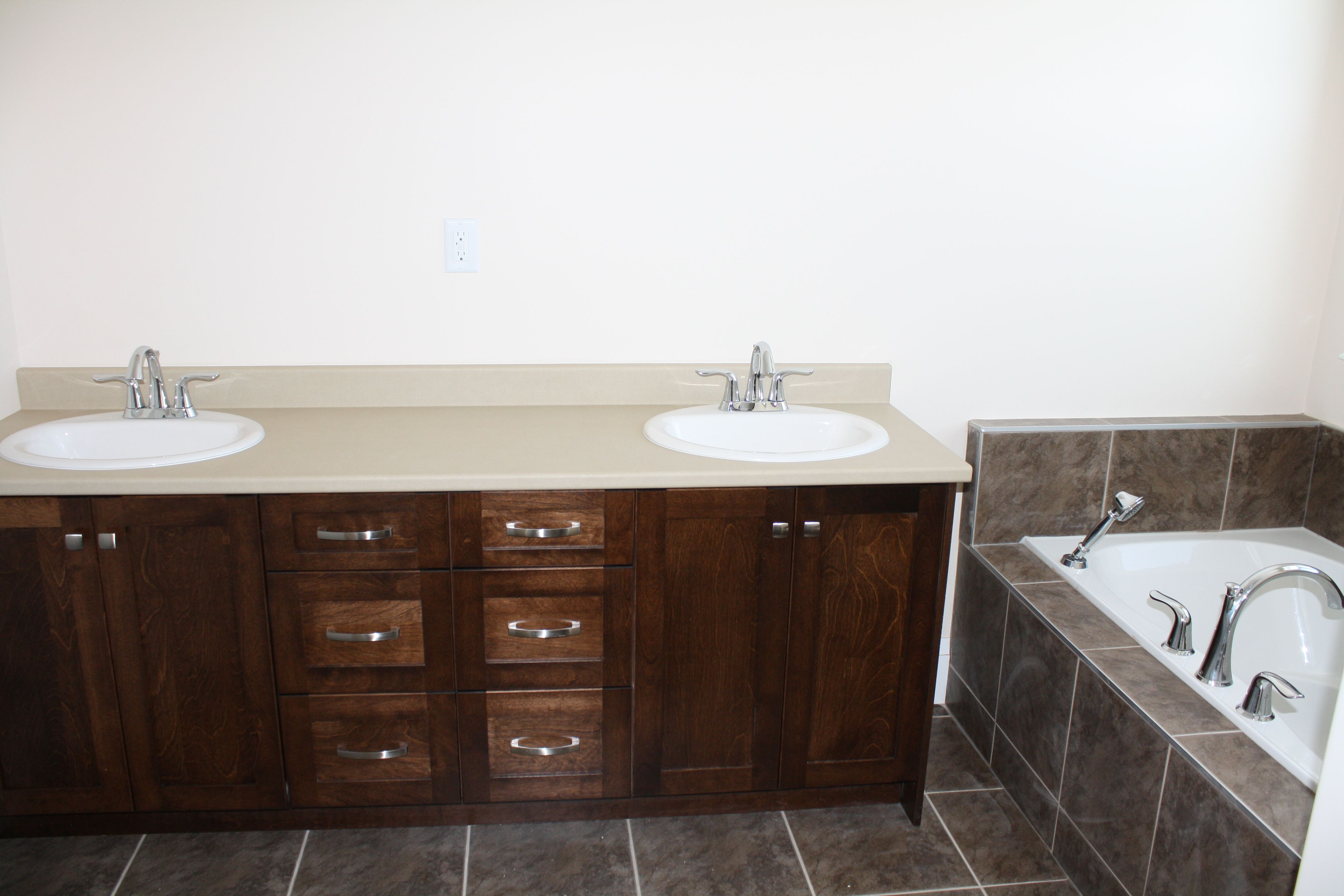 Double vanity next to a corner drop-in bathtub. This is your blank ...