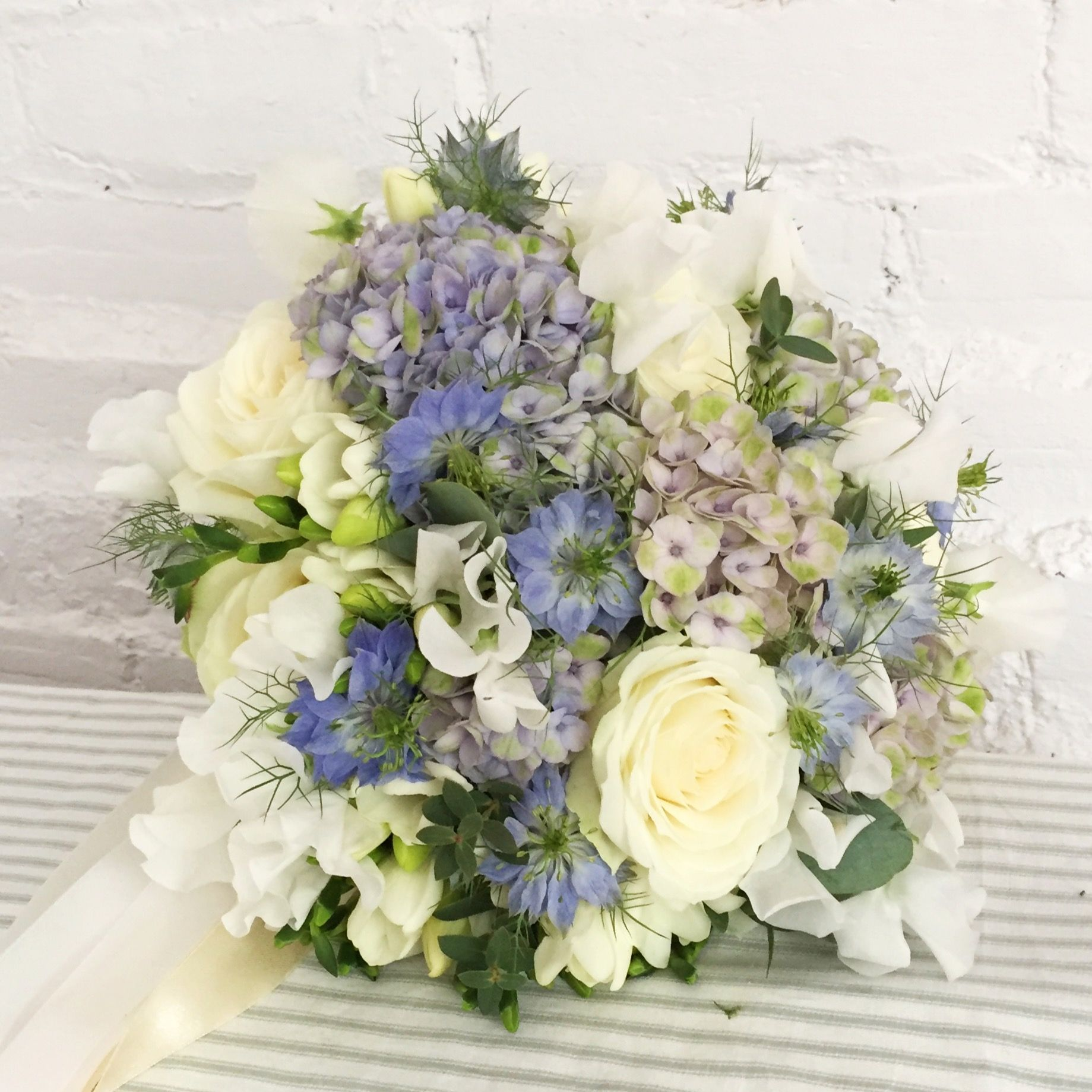 Hand tied summer bridal bouquet of whites and pale blue