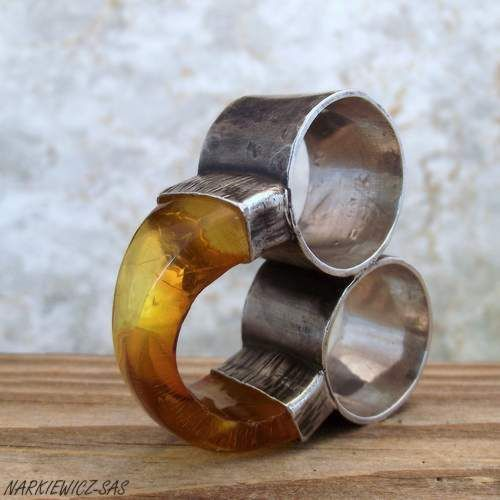 artist: Beata Narkiewicz-Sas - The Twins - silver two finger ring with amber The avant-garde ring made of 925 sterling silver and amber. Silver hammered, oxidized and rubbed. The two rings are connected together permanently. Width of each band: 1.7 cm. Rings have been connected by amber bridge. Amber: 0.5 cm thick, a width: 1 cm in the central part, 1.6 cm at both side.