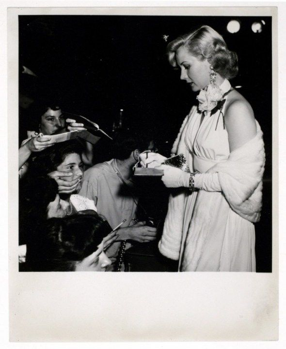 Weegee, [Movie star signing autographs at a movie premiere], ca. 1951