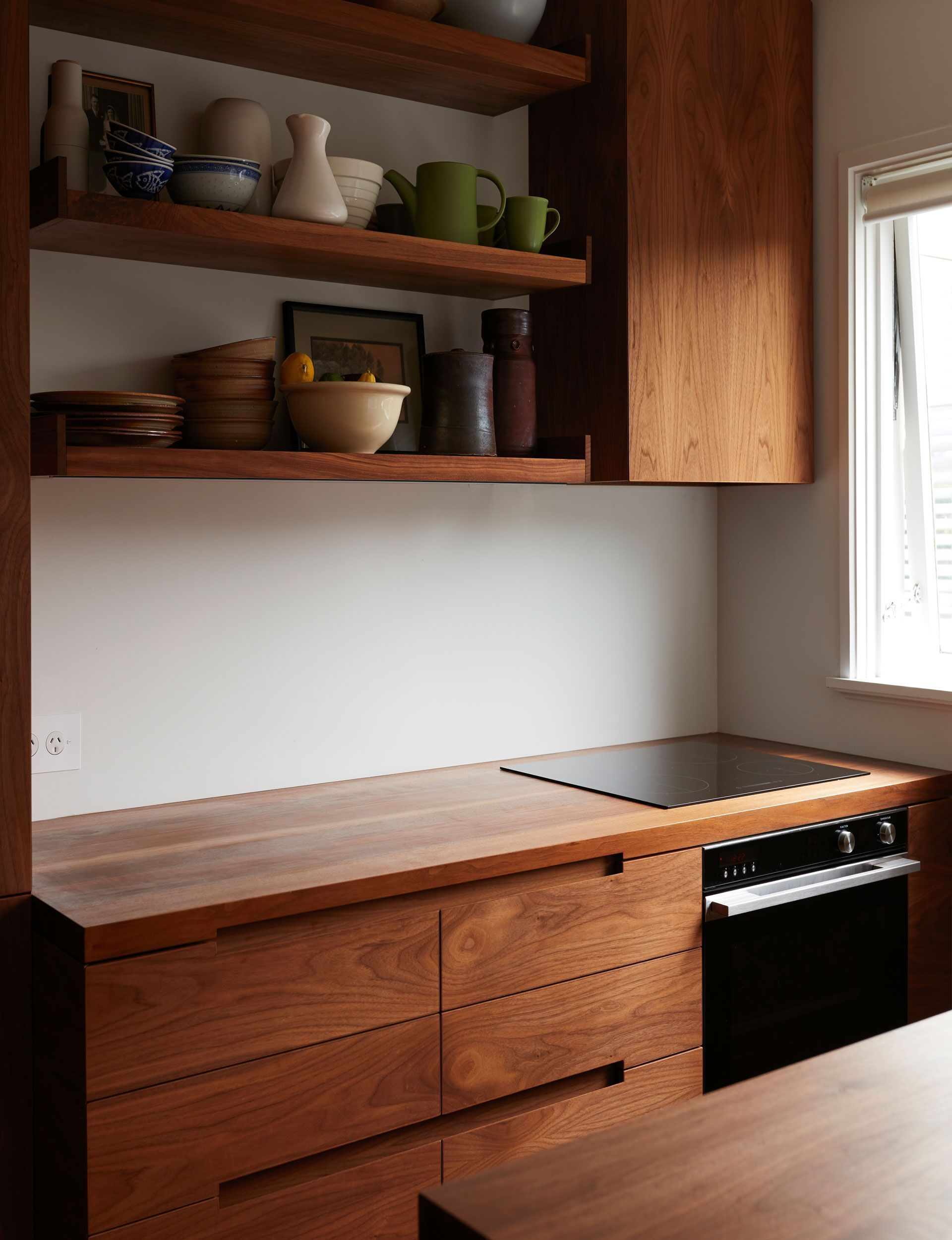 Photo of A small apartment kitchen is redesigned with rich walnut cabinetry