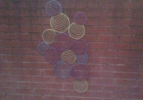 A piece of metal wall art, sanded and painted to match garden colours