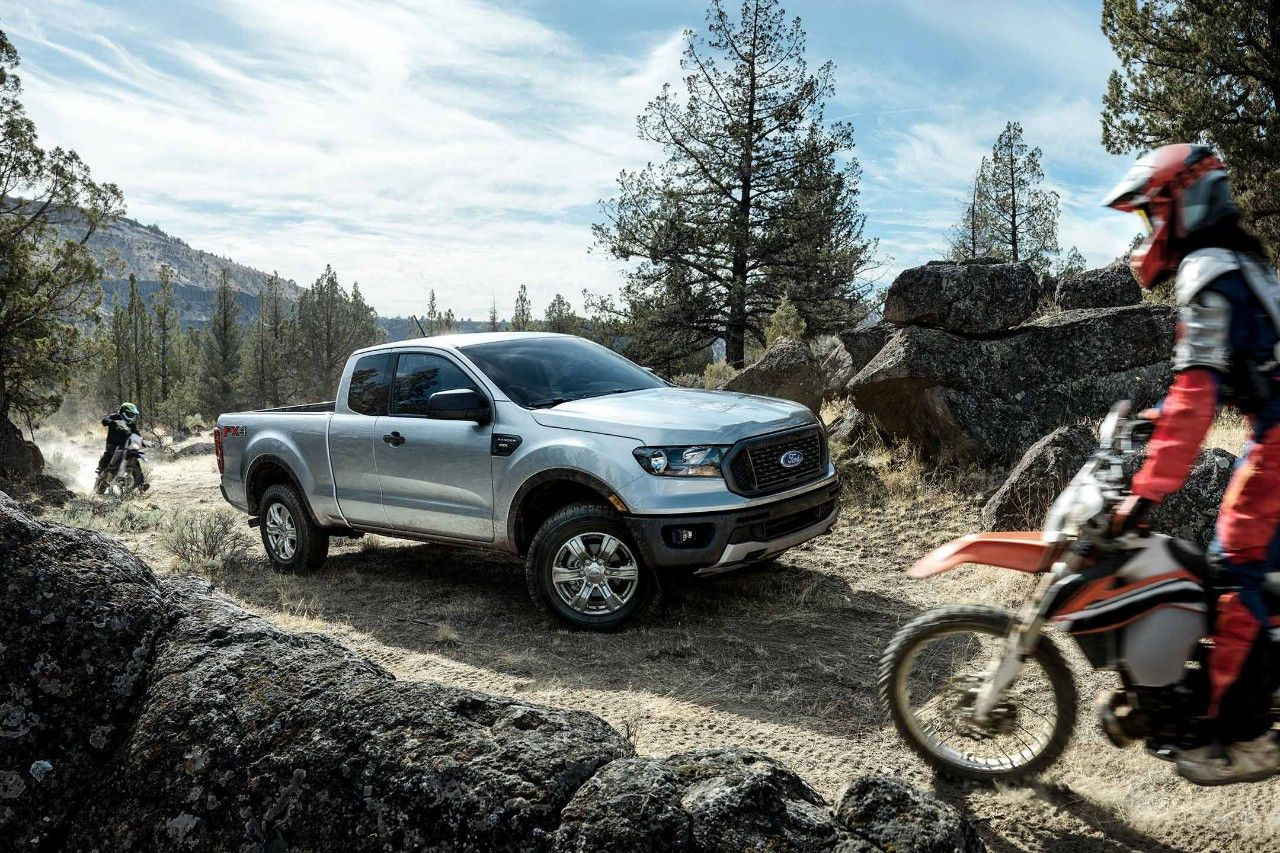 A 2019 Ford Ranger Xl Stx Fx4 Supercab In Silver On An Unpaved Road Stops For A Motorcyclist