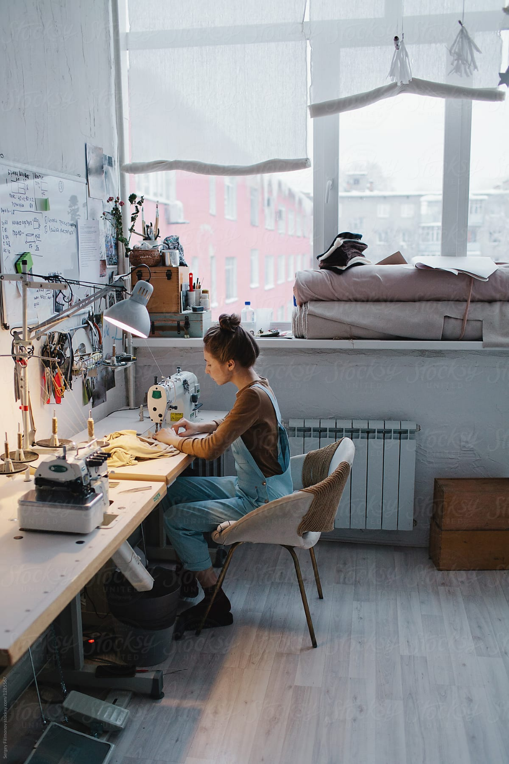 Young Woman Tailor Sewing While Sitting At Her Working Place In