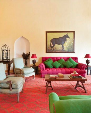 the colourful goa home of kitten and oliver musker - The painting of a nilgai above the Cliveden sofa was specially commissioned. The dhurrie was custom-made in Jaipur. All the furniture is from the Musker workshops.
