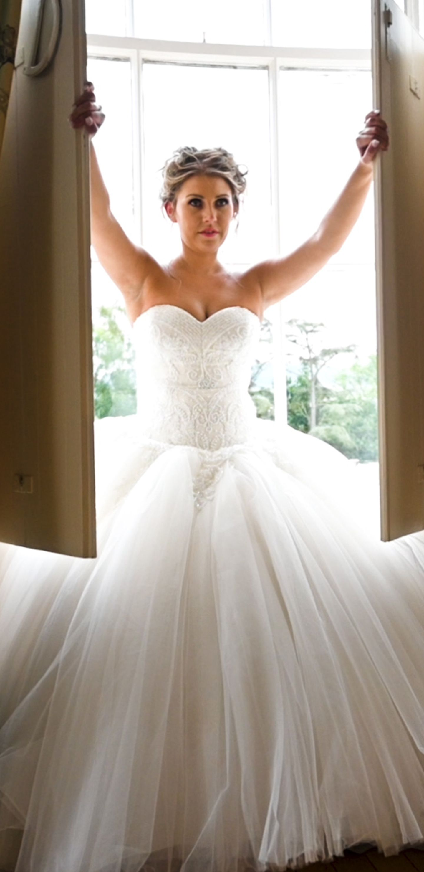 Bride in wedding dress standing in a window