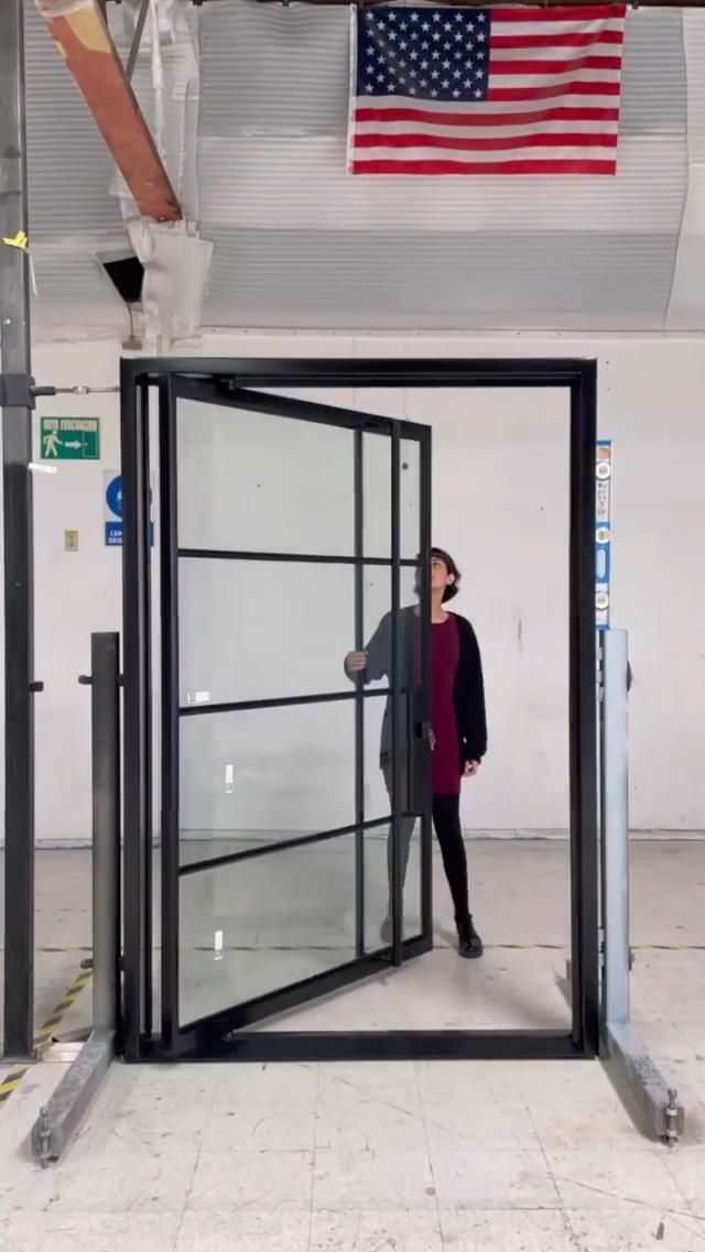 Sleek steel and glass custom-made pivot door for a spectacul…