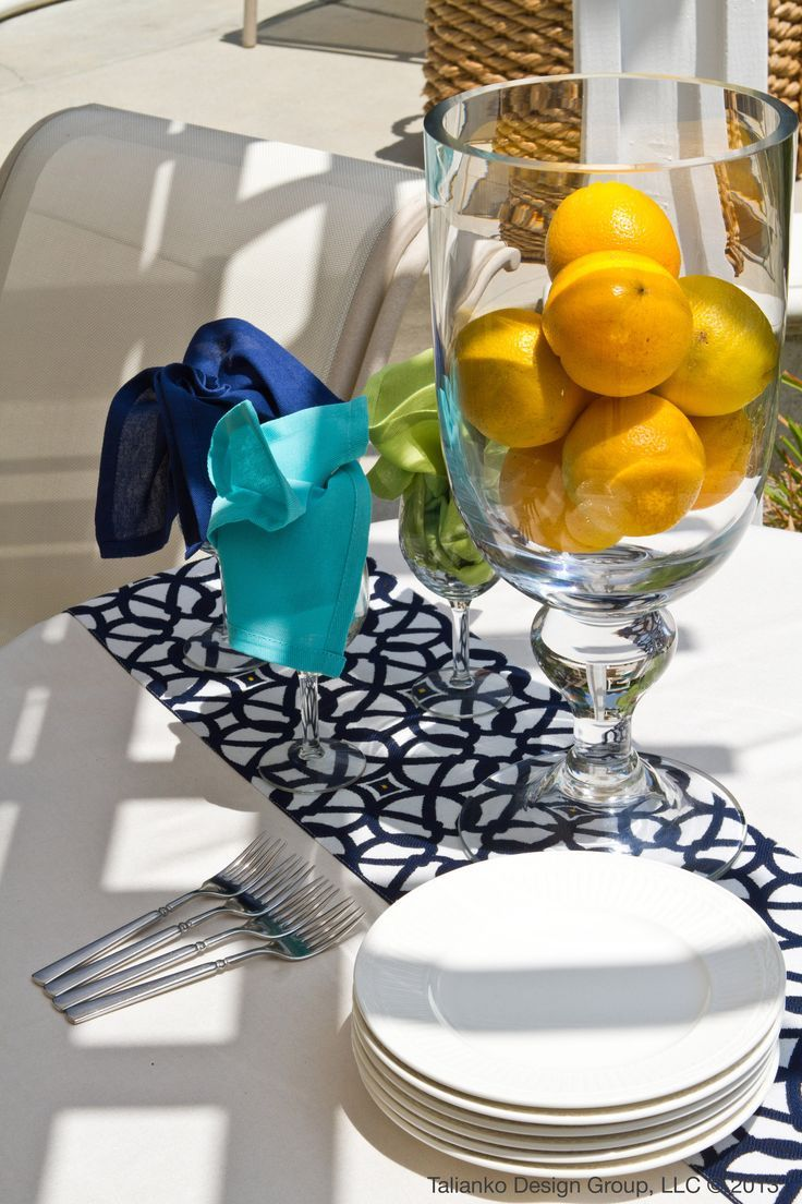 A dinner table in a backyard patio- perfect for family BBQs. Add fun colors to your backyard with fruit and napkins- and change it every season #summer #patio #blue #white #backyard #colors #colorful #design #interiordesign #diy
