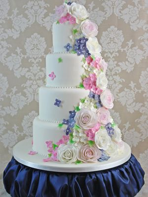Four tier white wedding cake with pink and purple edible sugar flowers - amazing uk wedding cakes - wedding cake ideas and pictures - food - allaboutyou.com