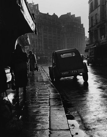 . A classic French 1950's scene.The familiar ass-high shape of a Citroen 2CV casts a shadow on a wet side-street. The 2CV was manufactured from 1948 through 1990, making it one of the most successful economy cars of all time.