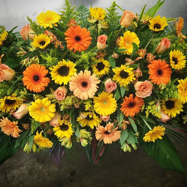 Full Casket Spray from our Parkallen location. Yellow, Orange and Peach tones with gerberas sunflowers, roses and alstroemeria.